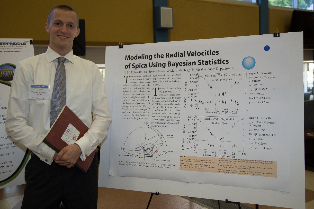 A student standing next to his poster